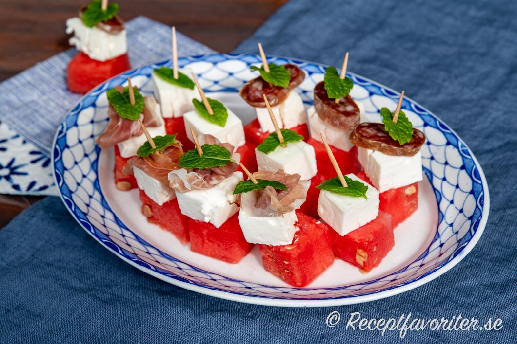 Tilltugg med vattenmelon och fetaost toppad med lufttorkad skinka och salami samt myntablad.