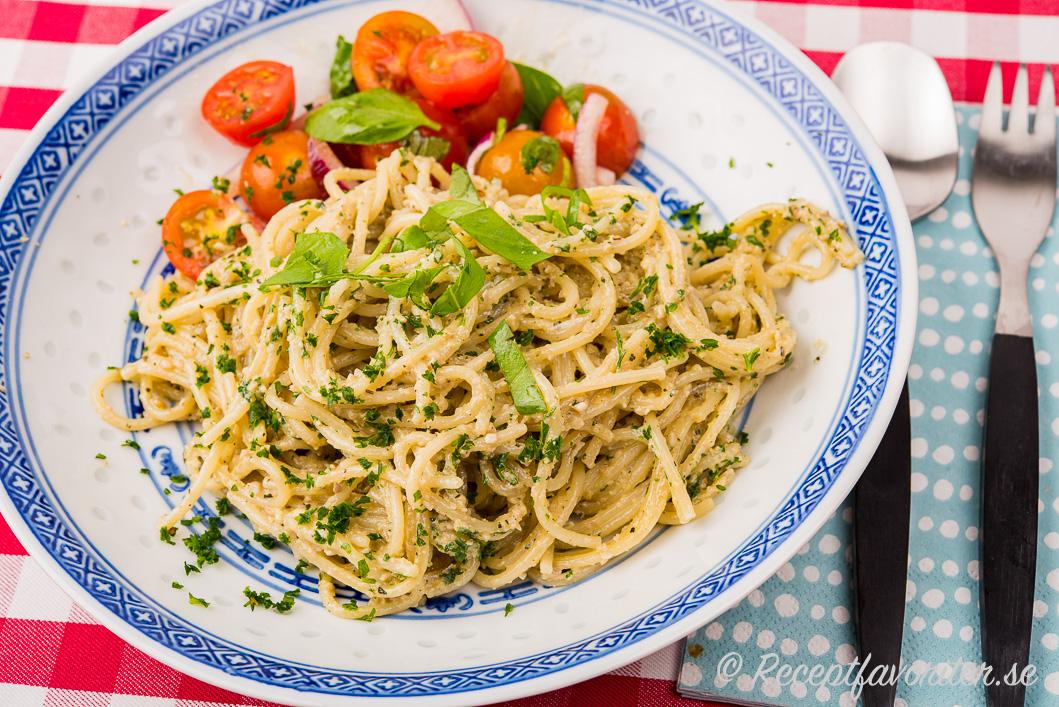 Vegan spagetti med solrospesto garnerad med färsk basilika.
