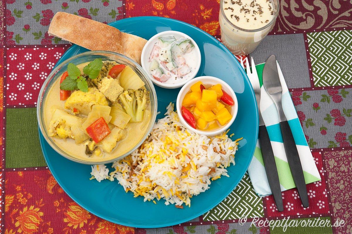 Vegansk currygryta med vegansk raita, picklad het mango och indiskt ris. Naan-bröd passar också till.