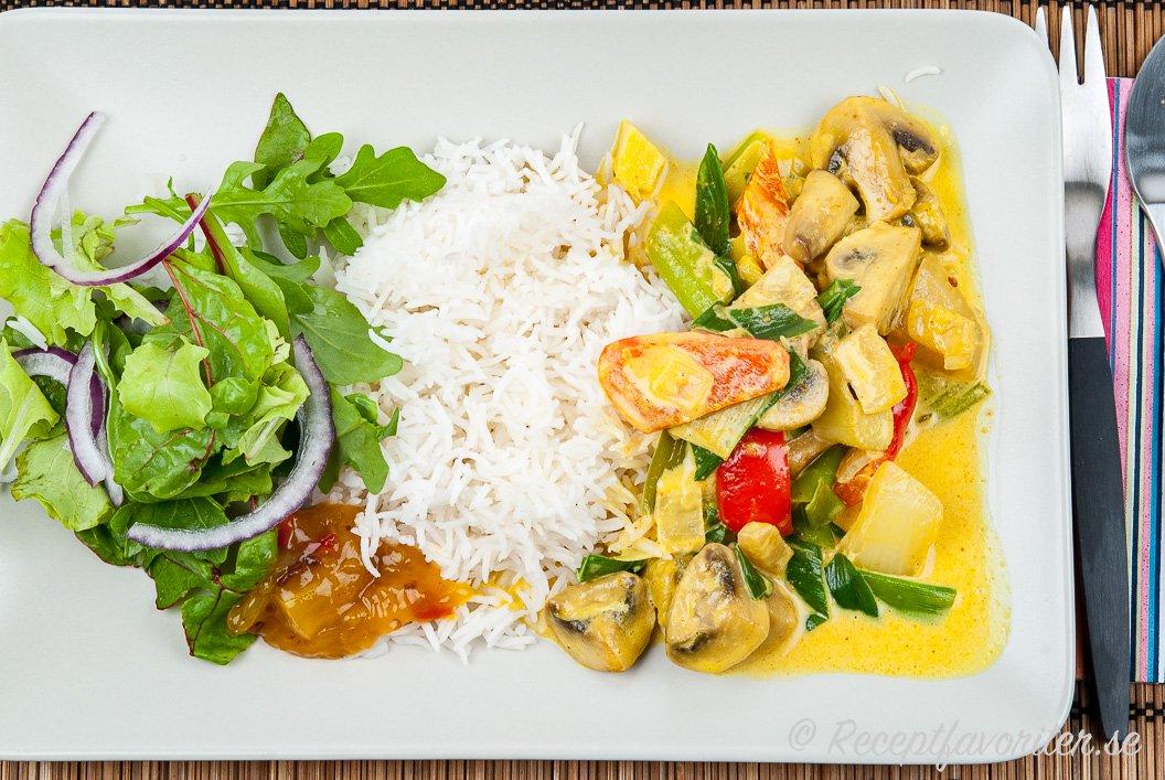 Vegetarisk currygryta med grönsaker serverad med ris, chutney och grönsallad på tallrik.
