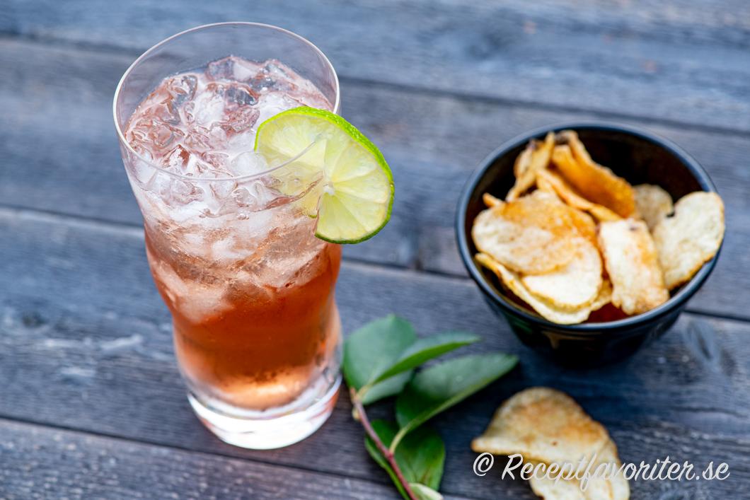 Vodka Cranberry i highballglas med is och lime serverad med lantchips.