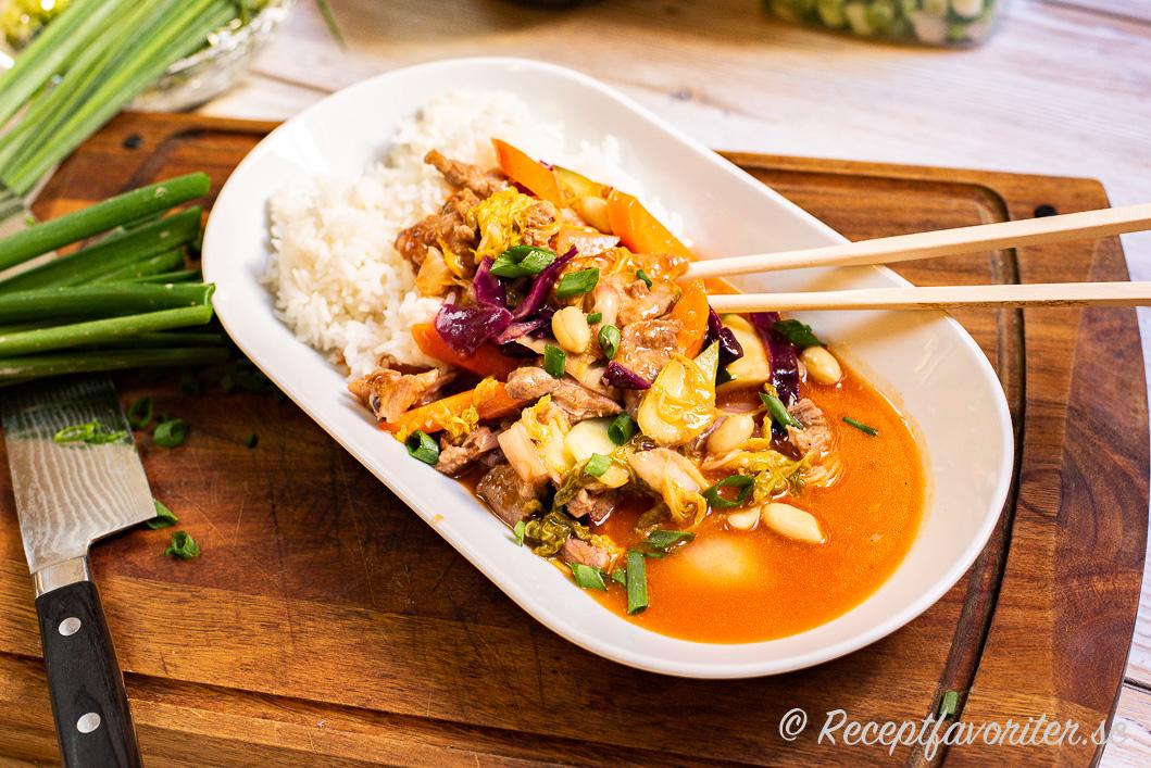 Woka marinerad fläskkarré med sötsur sås, jordnötter och grönsaker samt servera med ris.